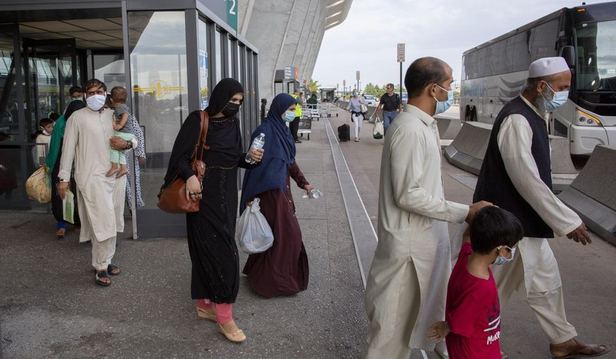 In this Tuesday, Aug. 31, 2021, file photo, families evacuated from Kabul, Afghanistan, walk to board a bus after they arrived at Washington Dulles International Airport, in Chantilly, Va. (AP Photo/Gemunu Amarasinghe, File)  **FILE**