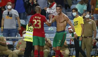 Portugal's Cristiano Ronaldo, right, celebrates after scoring his side's second goal during the World Cup 2022 group A qualifying soccer match between Portugal and the Republic of Ireland at the Algarve stadium outside Faro, Portugal, Wednesday, Sept. 1, 2021. (AP Photo/Armando Franca)