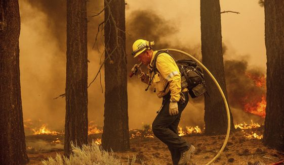 A firefighter battles the Caldor Fire along Highway 89, Tuesday, Aug. 31, 2021, near South Lake Tahoe, Calif. (AP Photo/Noah Berger)