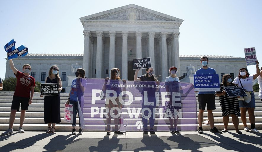 FILE - In this June 29, 2020 file photo, Anti-abortion protesters wait outside the Supreme Court for a decision, in Washington on the Louisiana case, Russo v. June Medical Services LLC. Even before a strict abortion ban took effect in Texas this week, clinics in neighboring states were fielding more and more calls from women desperate for options. he Texas law, allowed to stand in a decision Thursday, Sept. 2, 2021 by the U.S. Supreme Court, bans abortions after a fetal heartbeat can be detected, typically around six weeks. (AP Photo/Patrick Semansky)