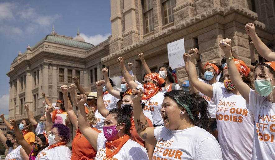 In this Sept. 1, 2021 file photo, women protest against the six-week abortion ban at the Capitol in Austin, Texas. Even before a strict abortion ban took effect in Texas this week, clinics in neighboring states were fielding more and more calls from women desperate for options. The Texas law, allowed to stand in a decision Thursday, Sept. 2, 2021 by the U.S. Supreme Court, bans abortions after a fetal heartbeat can be detected, typically around six weeks. (Jay Janner/Austin American-Statesman via AP File) **FILE**
