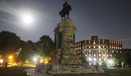 The moon illuminates the statue of Confederate General Robert E. Lee on Monument Avenue Friday June 5, 2020, in Richmond, Va. The Supreme Court of Virginia ruled Thursday, Sept 2, 2021, that the state can take down an enormous statue that has towered over Monument Avenue in the state's capital for more than a century and has become a symbol of racial injustice. (AP Photo/Steve Helber) **FILE**