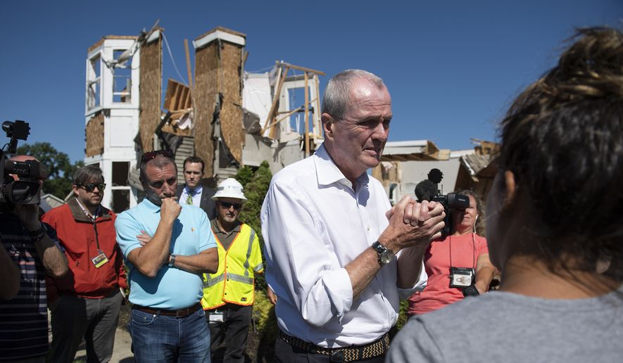 Gov. Phil Murphy speaks with Ashley and Troy Thomas on Thursday, Sept. 2, 2021, after their home was severely damaged by a tornado in Mullica Hill, N.J. A stunned U.S. East Coast woke up Thursday to a rising death toll, surging rivers and destruction after the remnants of Hurricane Ida walloped the region with record-breaking rain, filling low-lying apartments with water and turning roads into car-swallowing canals. (Joe Lamberti /Camden Courier-Post via AP)