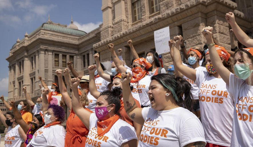 In this Sept. 1, 2021 file photo, women protest against the six-week abortion ban at the Capitol in Austin, Texas. Even before a strict abortion ban took effect in Texas this week, clinics in neighboring states were fielding more and more calls from women desperate for options. The Texas law, allowed to stand in a decision Thursday, Sept. 2, 2021 by the U.S. Supreme Court, bans abortions after a fetal heartbeat can be detected, typically around six weeks. (Jay Janner/Austin American-Statesman via AP) **FILE**