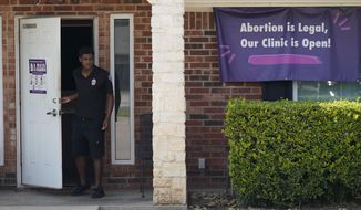 In this Sept. 1, 2021 file photo, a security guard opens the door to the Whole Women's Health Clinic in Fort Worth, Texas.  (AP Photo/LM Otero)  **FILE**