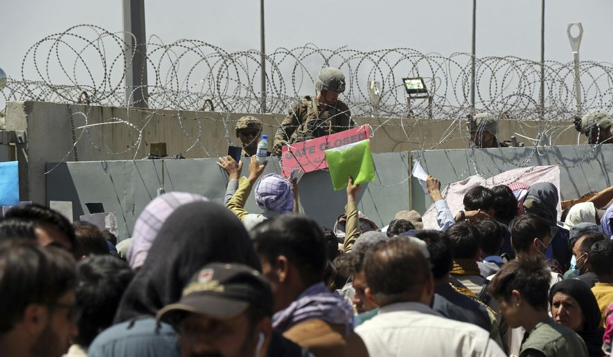 In this Aug. 26, 2021, file photo, a U.S. soldier holds a sign indicating a gate is closed as hundreds of people gather near an evacuation control checkpoint on the perimeter of the Hamid Karzai International Airport, in Kabul, Afghanistan. (AP Photo/Wali Sabawoon, File)