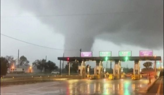 In this image taken from video provided by Scott Smith, a fast-moving tornado is seen in the distance through a windshield just before the toll booth for the Burlington Bristol Bridge on Wednesday, Sept. 1, 2021, in Burlington, N.J. (Scott Smith via AP)