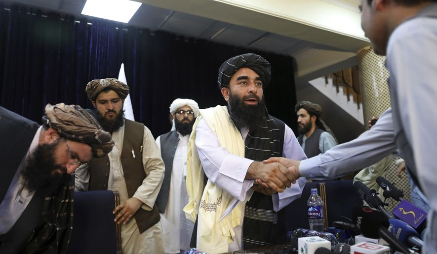 In this Aug. 17, 2021, photo, Taliban spokesman Zabihullah Mujahid, shakes hands with a journalist after his first news conference, in Kabul, Afghanistan. Mujahid vowed that the Taliban would respect women's rights, forgive those who resisted them and ensure a secure Afghanistan as part of a publicity blitz aimed at convincing world powers and a fearful population that they have changed. (AP Photo/Rahmat Gul) **FILE**