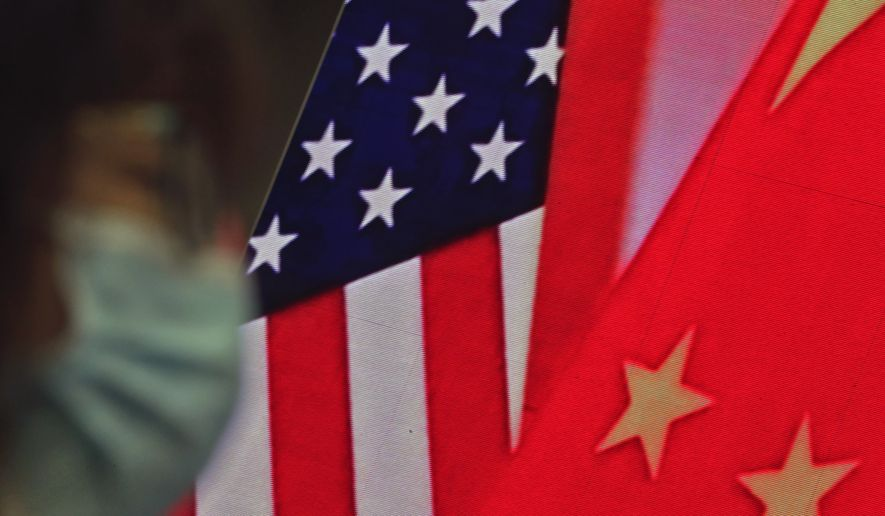 In this Feb. 22, 2021, photo, a woman wearing a face mask to help curb the spread of the coronavirus sits near a screen showing China and U.S. flags as she listens to a speech by Chinese Foreign Minister Wang Yi at the Lanting Forum on bringing China-U.S. relations back to the right track, at the Ministry of Foreign Affairs office in Beijing. (AP Photo/Andy Wong) **FILE**