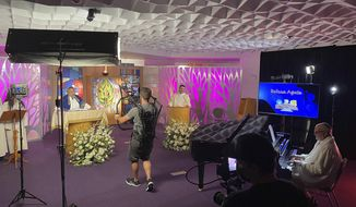 """In this August 2021 photo provided by Steve Pearlman, Rabbi Noah Farkas and Cantor Phil Baron tape a musical rendition of Oseh Shalom for the Rosh Hoshanah service from the """"pop up"""" High Holiday TV Studio on the Valley Beth Shalom campus in Encino, Calif. """"All of us were hoping this holiday season was going to be a do-over from 2020,"""" Farkas says. """"After all the pain, all the distancing, I was hoping we could shake it off, and everyone could come back and give each other hugs. That's not going to happen."""" (Steve Pearlman via AP)"""