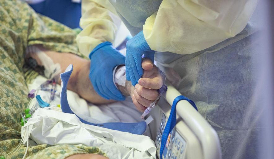 An R.N. holds the hand of a COVID-19 patient in the Medical Intensive care unit (MICU) at St. Luke's Boise Medical Center in Boise, Idaho on Tuesday, Aug. 31, 2021. More than half of the patients in the ICU are COVID-19 positive, none of which are vaccinated. (AP Photo/Kyle Green)