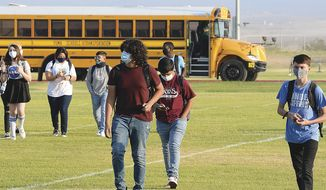 In this Sept. 17, 2020, file photo, students in face masks arrive on the Gila Ridge High School campus on the second first day of school, in Yuma, Ariz. (Randy Hoeft/The Yuma Sun via AP) ** FILE **