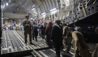 In this Aug. 22, 2021, file photo provided by the U.S. Air Force, Afghan passengers board a U.S. Air Force C-17 Globemaster III during the Afghanistan evacuation at Hamid Karzai International Airport in Kabul, Afghanistan. (MSgt. Donald R. Allen/U.S. Air Force via AP, File)