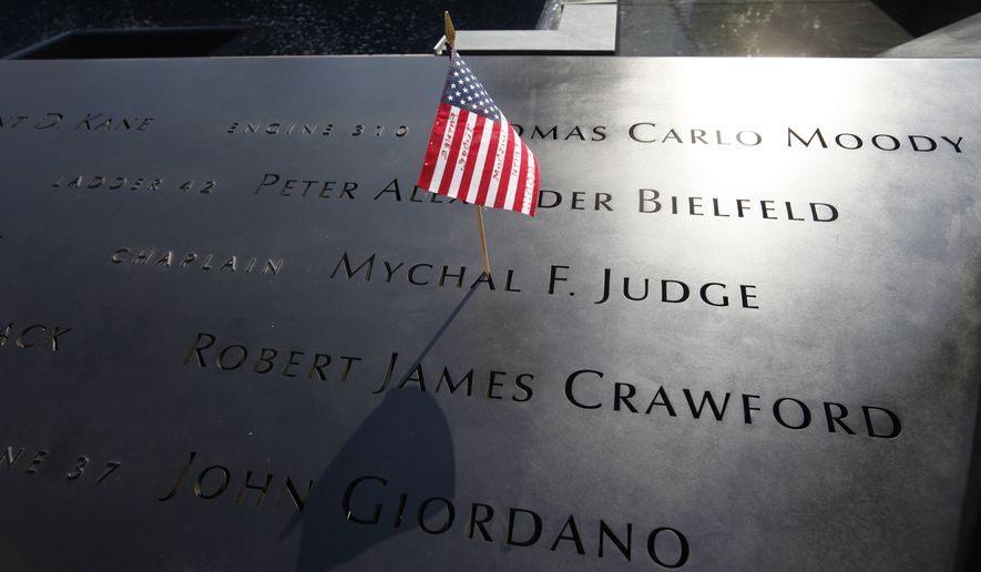 In this Monday, Sept. 12, 2011, file photo, a U.S. flag is stuck into the etched name of Father Mychal F. Judge, the New York Fire Department chaplain who died in the 9/11 attacks on the World Trade Center, at the National September 11 Memorial in New York. (AP Photo/Mike Segar, Pool) ** FILE **