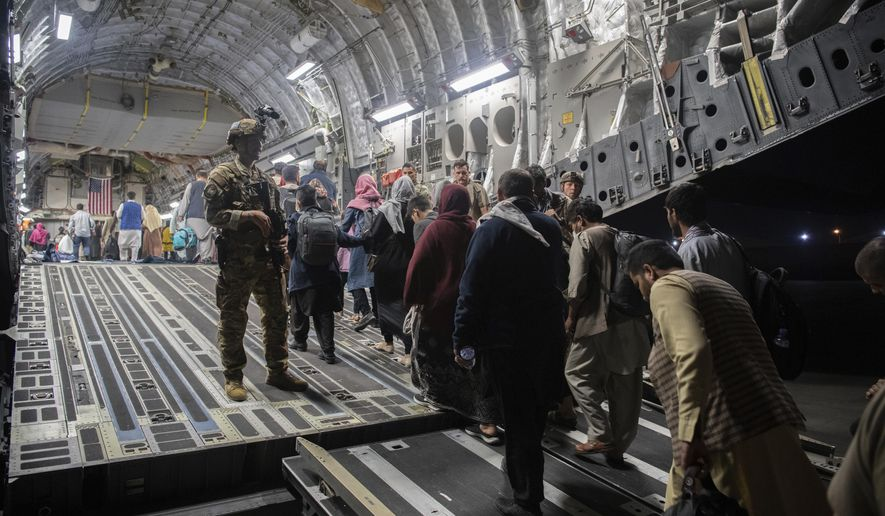 In this Aug. 22, 2021, photo provided by the U.S. Air Force, Afghan passengers board a U.S. Air Force C-17 Globemaster III during the Afghanistan evacuation at Hamid Karzai International Airport in Kabul, Afghanistan. (MSgt. Donald R. Allen/U.S. Air Force via AP) **FILE**