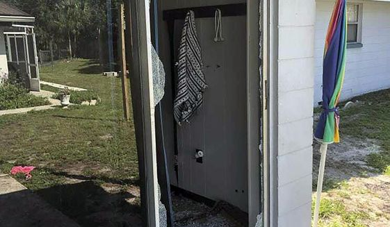 """This image provided by the Polk County Sheriff's Office shows the back of the residence where a Polk sheriff's lieutenant entered the house and exchanged fire with a shooting suspect in a neighborhood in Lakeland, Fla. Four people are dead including a mother who was still cradling her now-deceased baby in what Florida sheriff's deputies are calling a massive gunfight early Sunday with a suspect they said was """"ready for battle."""" (Polk County Sheriff's Office via AP)"""