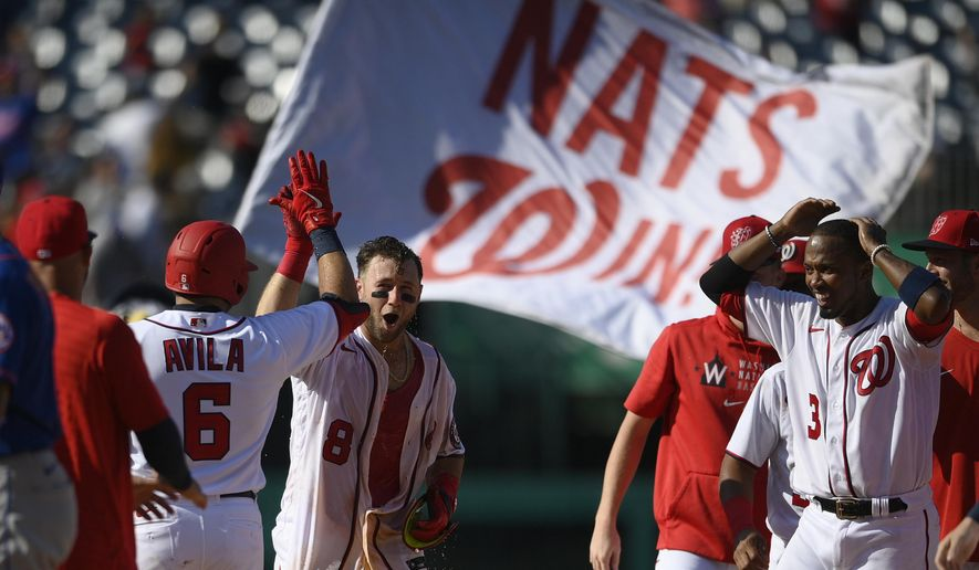 Washington Nationals' Carter Kieboom (8) high-fives Alex Avila (6) after hitting a walkoff single to drive in Josh Bell during the ninth inning of a baseball game against the New York Mets, Monday, Sept. 6, 2021, in Washington. Nationals' Alcides Escobar, right, looks on. (AP Photo/Nick Wass)