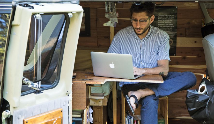 In this 2018 photo, Danny Fenster works out of his van that he made into a home/office in Detroit. The parents and brother of an American journalist who has been detained in Myanmar for 100 days are vowing to never stop working to secure his release (Fenster Family photo via AP)