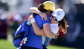 Europe's Leona Maguire celebrates with her sister Lisa after defeating United States' Jennifer Kupcho on the 15th hole during the singles matches at the Solheim Cup golf tournament, Monday, Sept. 6, 2021, in Toledo, Ohio. (AP Photo/David Dermer)