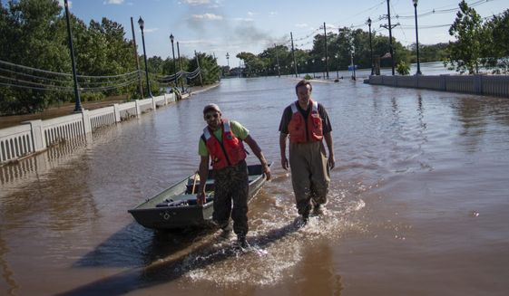 United States Geological Survey workers push a boat as they look for residents on a street flooded as a result of the remnants of Hurricane Ida in Somerville, NJ., Thursday, Sept. 2, 2021. (AP Photo/Eduardo Munoz Alvarez)