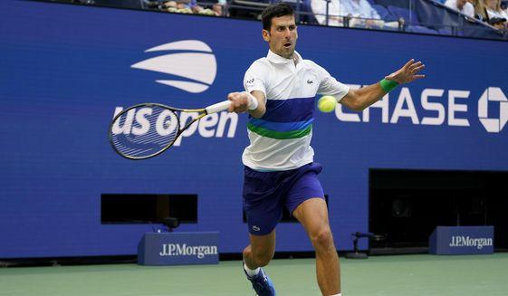 Novak Djokovic, of Serbia, returns a shot to Kei Nishikori, of Japan, during the third round of the US Open tennis championships, Saturday, Sept. 4, 2021, in New York. (AP Photo/John Minchillo)