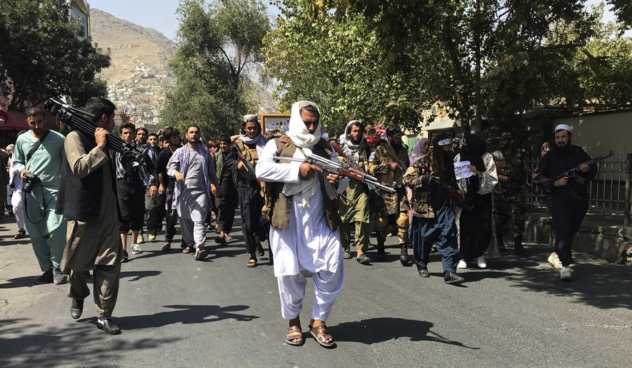 Taliban soldiers walk towards Afghans shouting slogans during an anti-Pakistan demonstration, near the Pakistan embassy in Kabul, Afghanistan, Tuesday, Sept. 7, 2021. (AP Photo/Wali Sabawoon)
