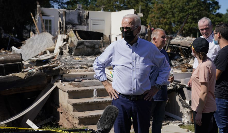 President Joe Biden speaks to members of the media as he tours a neighborhood impacted by Hurricane Ida, Tuesday, Sept. 7, 2021, in Manville, N.J. New Jersey Gov. Phil Murphy speaks to people, second from right.(AP Photo/Evan Vucci)