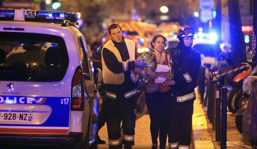 In this Nov. 13, 2015, file photo, rescue workers help a woman after a shooting, outside the Bataclan theater in Paris. France is putting on trial 20 men accused in the Nov. 13, 2015, Islamic State terror attacks on Paris that left 130 people dead and hundreds injured. Nine gunmen and suicide bombers struck within minutes of each other at the national soccer stadium, the Bataclan concert hall and restaurants and cafes. The lone survivor of the terror cell from that night is among those being tried for the deadliest attack in France since World War II. (AP Photo/Thibault Camus, File)