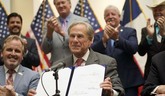 Texas Gov Greg Abbott shows off Senate Bill 1, also known as the election integrity bill, after he signed it into law in Tyler, Texas, Tuesday, Sept. 7, 2021. The sweeping bill signed Tuesday by the two-term Republican governor further tightens Texas' strict voting laws. (AP Photo/LM Otero)