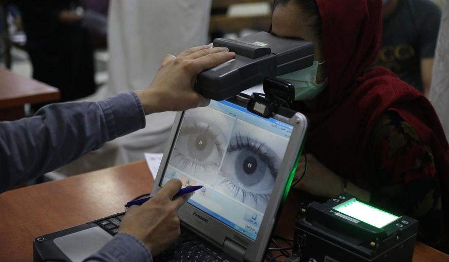 In this June 30, 2021, file photo, an employee scans the eyes of a woman for biometric data needed to apply for a passport, at the passport office in Kabul, Afghanistan. Over two decades, the United States and its allies spent hundreds of millions of dollars building databases for the Afghan people. (AP Photo/Rahmat Gul, File)