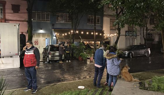 People gather outside on the sidewalk after a strong earthquake was felt, in the Roma neighborhood of Mexico City, Tuesday, Sept. 7, 2021. The quake struck southern Mexico near the resort of Acapulco, causing buildings to rock and sway in Mexico City nearly 200 miles away (AP Photo/Leslie Mazoch)