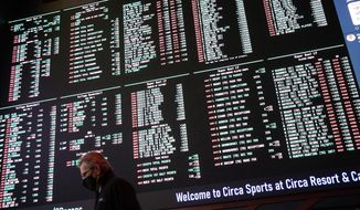 In this Feb. 3, 2021, file photo, a man walks by as betting odds for NFL football's Super Bowl 55 are displayed on monitors at the Circa resort and casino sports book in Las Vegas. Three years after the Supreme Court overturned the Professional and Amateur Sports Protection Act and allowed states to legalize sports betting, the NFL has embraced gambling as part of the landscape. (AP Photo/John Locher, File)