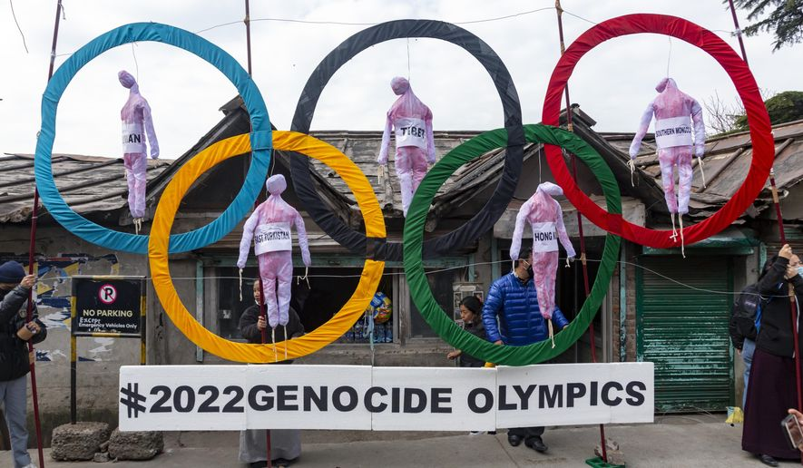 In this Feb. 3, 2021, file photo, exile Tibetans use the Olympic Rings as a prop as they hold a street protest against the holding of 2022 Winter Olympics in Beijing in Dharmsala, India. Some of the world's largest broadcasters including American network NBC are being asked to cancel plans to cover the 2022 Winter Olympics in Beijing over alleged human rights abuses in the country. The Games open on Feb. 4. (AP Photo/Ashwini Bhatia, File)