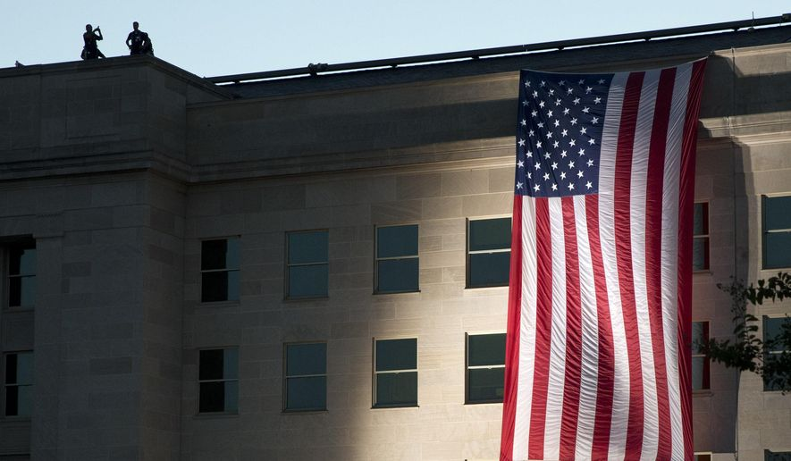 In this Sept. 11, 2015, file photo an American flag is draped on the side of the Pentagon where the building was attacked Sept. 11, 2001, on the 14th anniversary of the attack.  (AP Photo/Jacquelyn Martin, File)