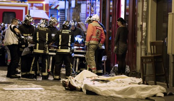 In this Nov. 13, 2015, file photo, medics stand by victims in a Paris restaurant, Friday, Nov. 13, 2015. On Nov. 13, 2015, a cell of nine Islamic State militants armed with automatic rifles and explosive vests left a trail of dead and injured at the national stadium, Paris bars and restaurants and the Bataclan concert hall. Nearly all the attackers were from France or Belgium, as were the cell's 10th member — the only one still alive. He is the chief defendant among 20 people charged in a trial that is expected to last nine months. (AP Photo/Thibault Camus, File)