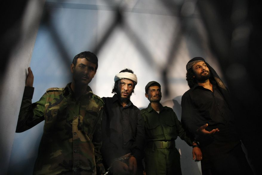 In this April 22, 2014, photo, a group of suspected al-Qaida militants accused of the killing of an army general in a suicide bombing stands trial at a state security court in Sanaa, Yemen. Over the past decade, even as it used Yemen as a base for international attacks, al-Qaida in the Arabian Peninsula has often clashed with the military and security forces, carrying out attacks and withstanding crackdowns even as it sought to weave itself into Yemeni society. (AP Photo/Hani Mohammed) **FILE**