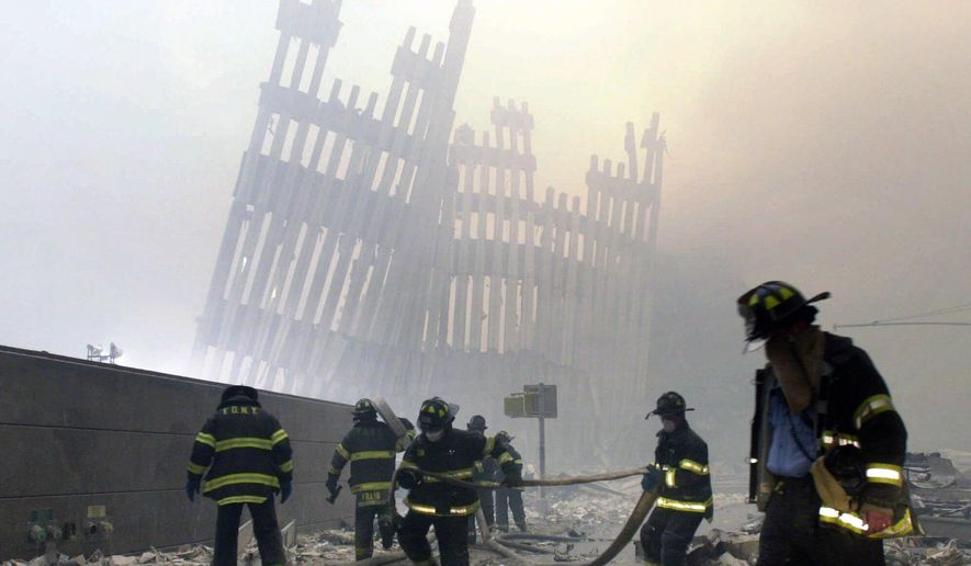 Firefighters work beneath the destroyed mullions, the vertical struts, of the World Trade Center in New York on Tuesday, Sept. 11, 2001. (AP Photo/Mark Lennihan) ** FILE **