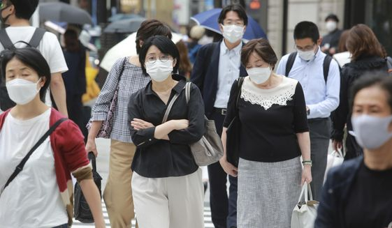 People wearing face masks to protect against the spread of the coronavirus walk on a street in Tokyo Wednesday, Sept. 8, 2021. (AP Photo/Koji Sasahara)
