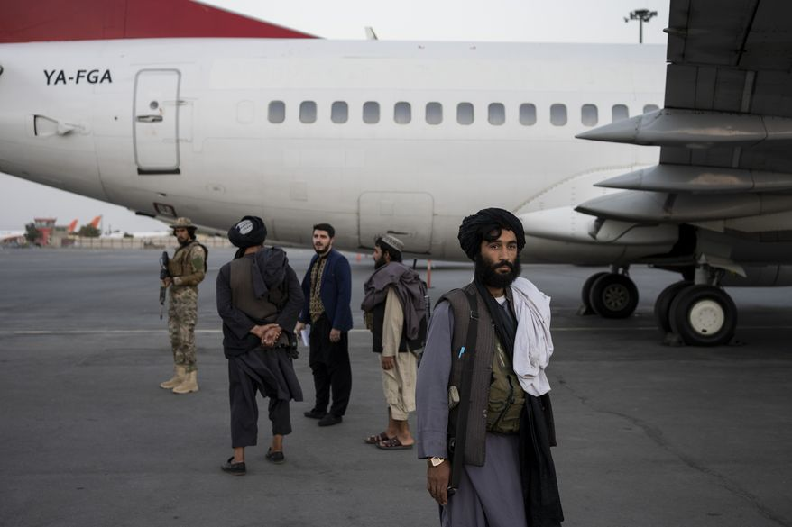 Taliban personnel stand beside a plane at the airport in Kabul, Afghanistan, Thursday, Sept. 9, 2021. Some 200 foreigners, including Americans, flew out of Afghanistan on an international commercial flight from Kabul airport on Thursday, the first such large-scale departure since U.S and foreign forces concluded their frantic withdrawal at the end of last month. (AP Photo/Bernat Armangue)