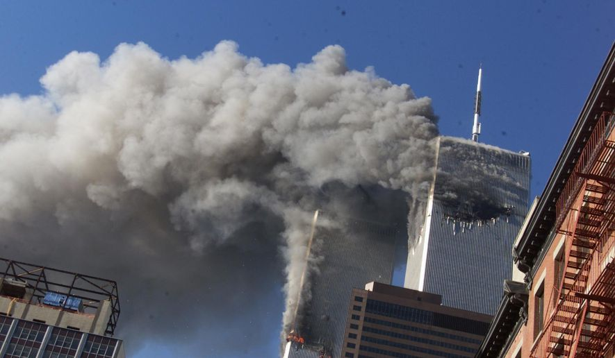 In this Sept. 11, 2001 photo, smoke rises from the burning twin towers of the World Trade Center after hijacked planes crashed into them, in New York City. (AP Photo/Richard Drew, File)
