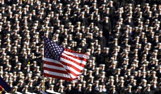 In this Dec. 1, 2001, file photo, the American flag flies with a background of Navy midshipmen during the national anthem at the 102nd Army Navy NCAA college football game in Philadelphia. Twenty years later, former Army football coach Todd Berry still gets choked up thinking about that Sept. 11, 2001, day and the terrorist attacks carried out not only on the twin towers at the World Trade Center but at the Pentagon, and in a field in rural Pennsylvania. (AP Photo/Chris Gardner, File) **FILE**