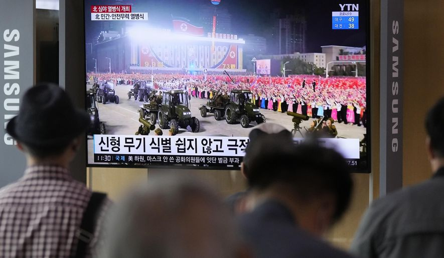 People watch a TV showing a military parade held in Pyongyang, North Korea, at Seoul Railway Station in Seoul, South Korea, Thursday, Sept. 9, 2021. North Korea paraded goose-stepping soldiers and military hardware in its capital overnight in a celebration of the nation's 73rd anniversary that was overseen by leader Kim Jong-un, state media reported Thursday. (AP Photo/Ahn Young-joon)