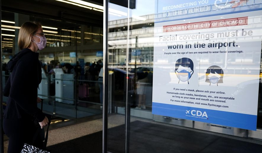 In this July 2, 2021 photo, a traveler walks in Terminal 3 as a sign stating face coverings are required is displayed at O'Hare International Airport in Chicago.  The leading U.S. airlines say that the rise in COVID-19 cases is hurting ticket sales and pushing back the recovery of the travel industry. American, United, Delta, Southwest and others reported setbacks in regulatory filings Thursday, Sept. 9. (AP Photo/Nam Y. Huh) **FILE**