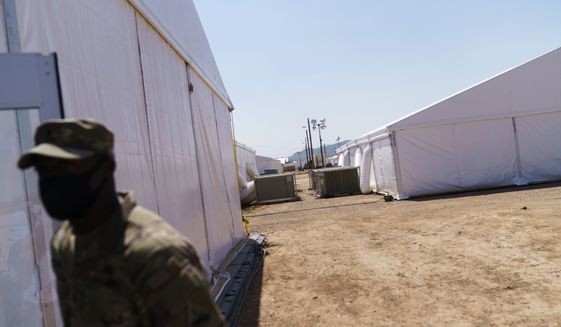 A soldier stands outside tents at Fort Bliss' Doña Ana Village where Afghan refugees are being housed in Chaparral, N.M., Friday, Sept. 10, 2021. The Biden administration provided the first public look inside the U.S. military base where Afghans airlifted out of Afghanistan are screened, amid questions about how the government is caring for the refugees and vetting them. (AP Photo/David Goldman)