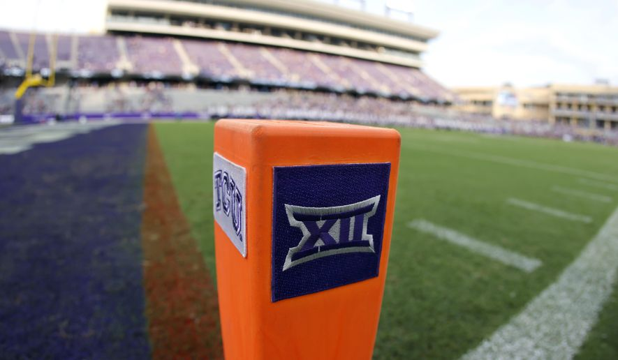 In this Saturday, Sept. 4, 2021, file photo, a Big 12 Conference logo is displayed on a goal line pylon before Duquesne played TCU in an NCAA college football game, in Fort Worth, Texas. The Big 12 has extended membership invitations to BYU, UCF, Cincinnati and Houston to join the Power Five league. That comes in advance of the league losing Oklahoma and Texas to the Southeastern Conference. (AP Photo/Ron Jenkins, File) **FILE**
