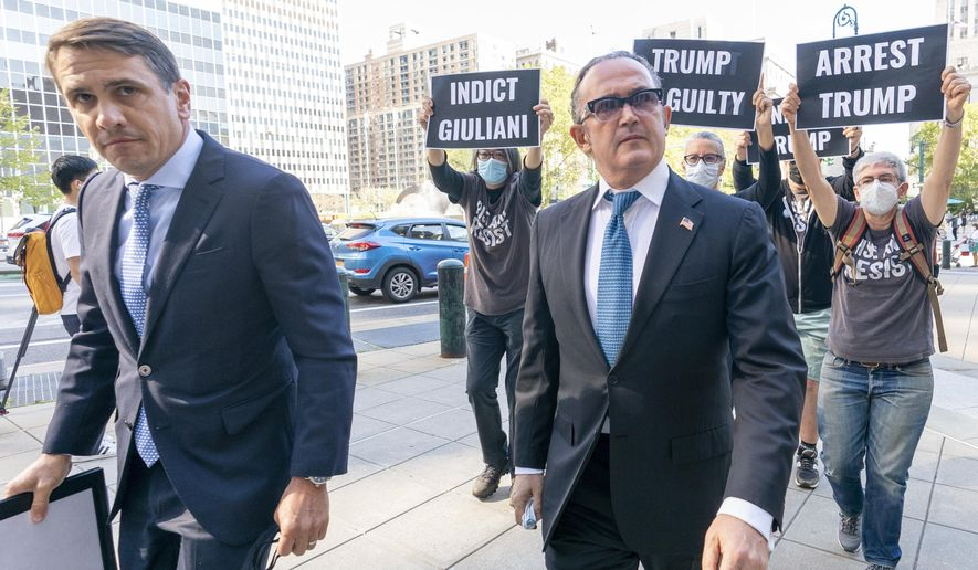 Activist with Rise and Resist follow Igor Fruman, right, as he arrives in Federal court in Manhattan with his attorney Todd Blanche, Friday, Sept. 10, 2021 in New York.  Fruman, a businessman who helped Rudy Giuliani in his effort to dig up dirt on Joe Biden in Ukraine, is scheduled to appear in court for an expected guilty plea in a case involving allegations of illegal campaign contributions (AP Photo/Mary Altaffer)