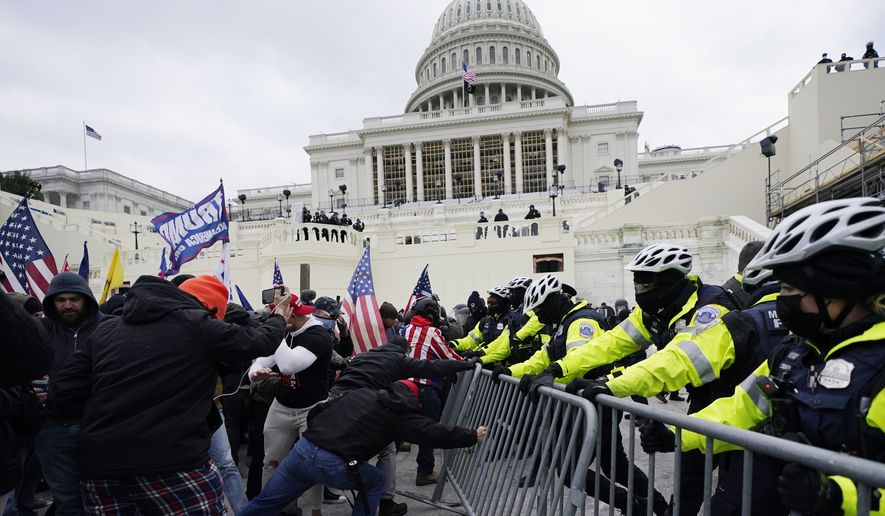Trump supporters try to break through a police barrier, Wednesday, Jan. 6, 2021, at the Capitol in Washington. (AP Photo/Julio Cortez, File)