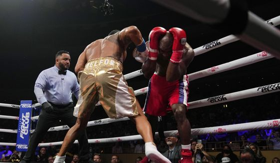 Former heavyweight champion Evander Holyfield, right, shields himself from punches by former MMA star Vitor Belfort, before the boxing bout was stopped in the first round Saturday, Sept. 11, 2021, in Hollywood, Fla. (AP Photo/Rebecca Blackwell) **FILE**