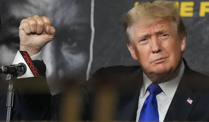 Former President Donald Trump salutes cheering fans as he prepares to provide commentary for a boxing event headlined by a bout between former heavyweight champ Evander Holyfield and former MMA star Vitor Belfort, Saturday, Sept. 11, 2021, in Hollywood, Fla. (AP Photo/Rebecca Blackwell) **FILE**