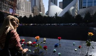 Mourners gather at the north pool adorned with flowers during ceremonies to commemorate the 20th anniversary of the Sept. 11, 2001 terrorist attacks, Saturday, Sept. 11, 2021, at the National September 11 Memorial & Museum in New York. (AP Photo/John Minchillo)